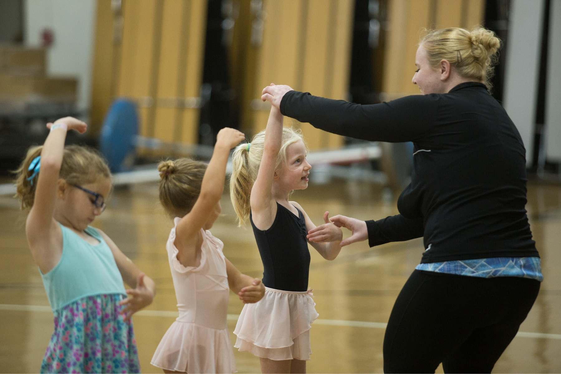 instructor helps dance student